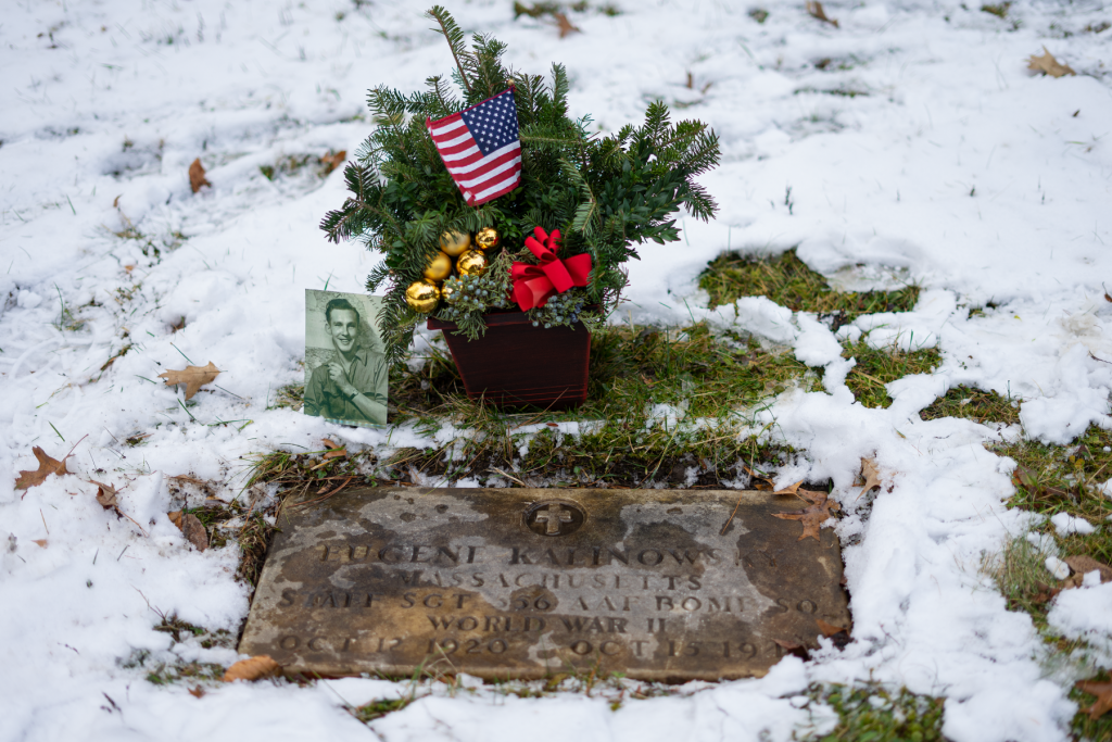 """A small black and white photo of a smiling young man and a decorative holiday planter of evergreen tree branches with gold bells, an American flag, and a red ribbon sit above a grave marker. There is a light snow on the ground and the grave marker reads """"Eugene Kalinowski."""""""
