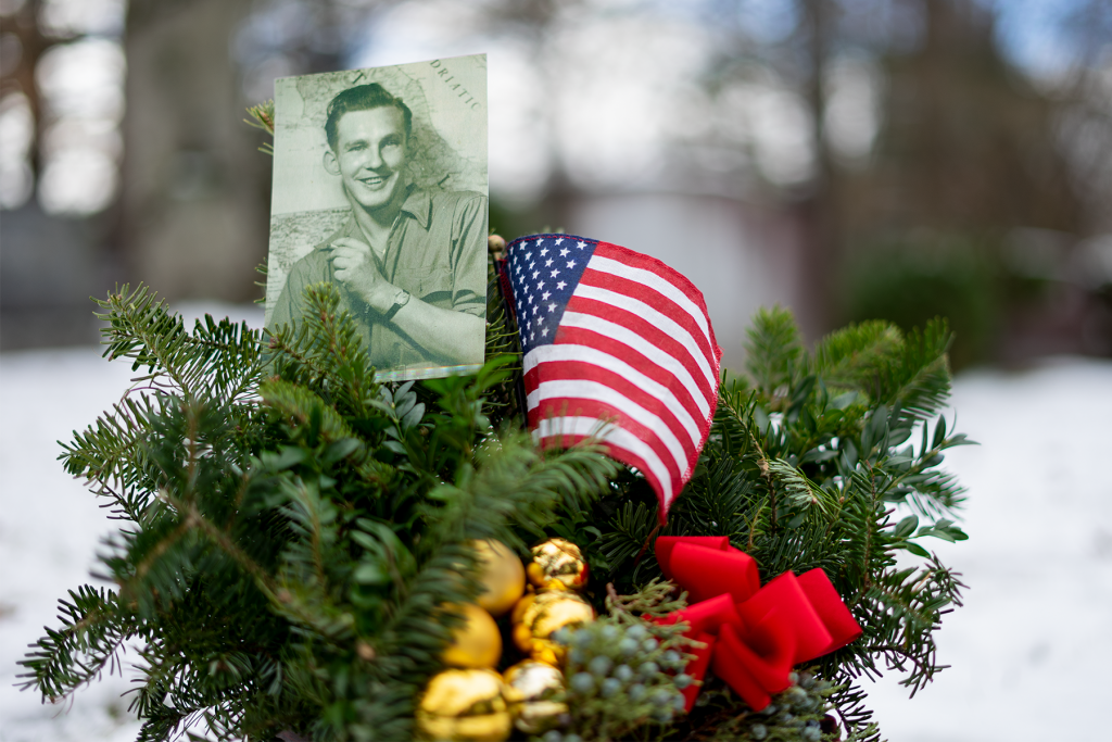 A small black and white photo of a smiling young man is perched in a decorative holiday planter of evergreen tree branches with gold bells, an American flag, and a red ribbon.