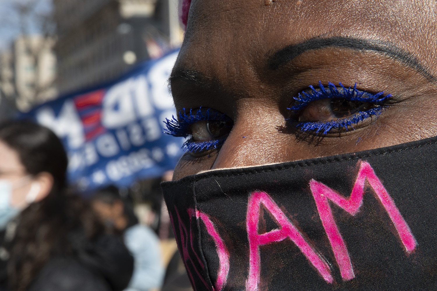 Close-up image of a black woman from her forehead to her mouth. She wears bright blue eyeliner and a black mask with the letters DAM in pink paint on the fabric. She looks directly at the camera, while behind her is a crowd and a blury Biden for President flag.