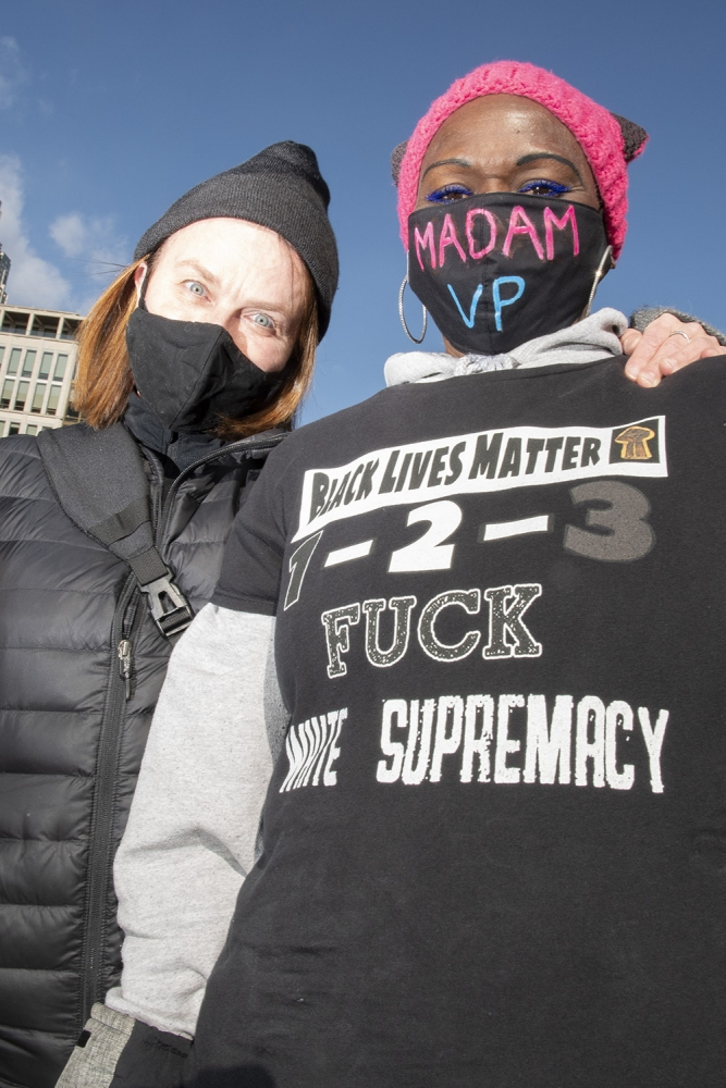 "A white woman with red hair, a black facemask, and a black winter hat and jacket stands with her hand on a black woman's shoulder. The black woman is wearing a pink pussy-style knit hat, a black mask with the words Madam VP, and a grey sweatshirt with a black shirt over it. The shirt says ""Black Lives Matter / 1-2-3 / Fuck White Supremacy."""
