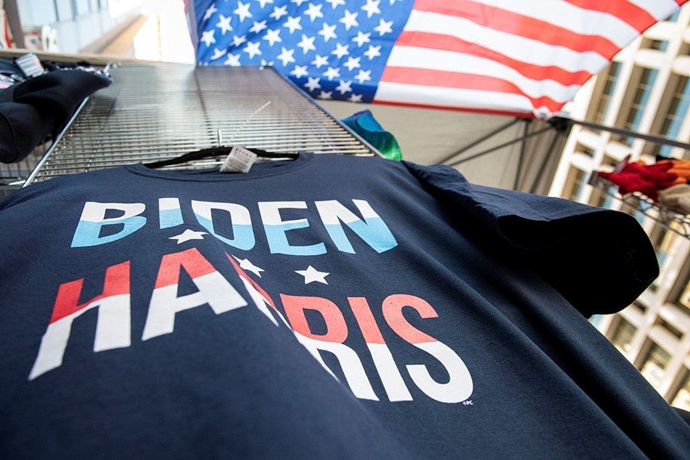 A navy blue shirt, bearing the words BIDEN HARRIS sits on a wire rack, behind is part of an American flag.