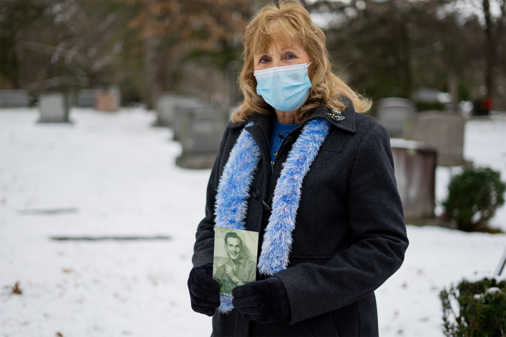 A white woman with blonde hair wearing a blue face mask, blue scarf, black winter coat, and black gloves stands in a snow-covered cemetary, holding a black and white photograph of a young man.