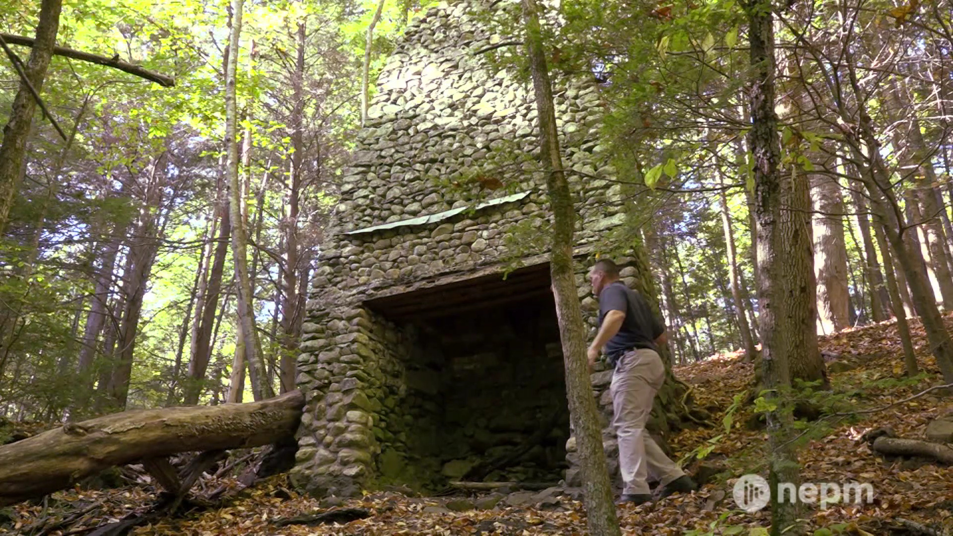 Image of a man climbing near the ruins of a rock building surrounded by trees in West Springfield's Bear Hole.