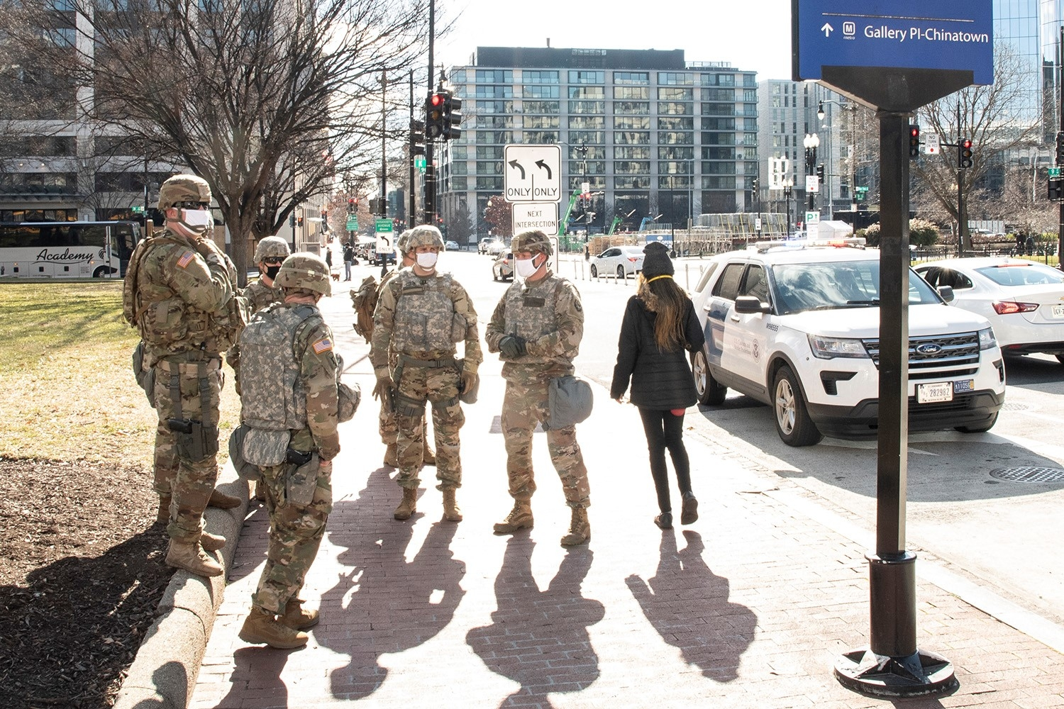 A group of military personal, wearing camoflage fatigues, stands on a sidewalk near an active street in downton Washington, D.C. A woman wearing a black jacket, pants, and hat, walks past them.