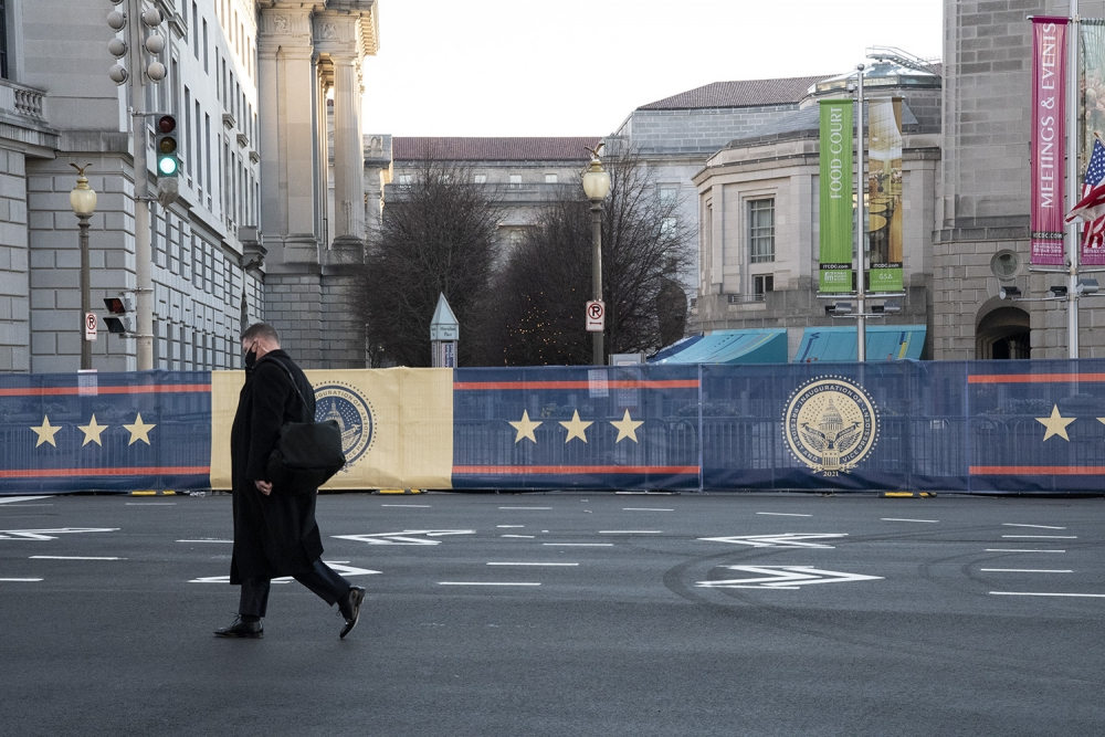 A white man wearing a black winter jacket, carrying a black duffel bag, and dressed in a suit walks along a mostly deserted street. Behind him are white stone buildings. In front of the buildings are presidential banners in gold, navy blue, and red.