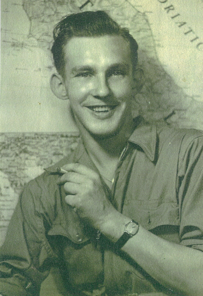 A black and white photo featuring a young man with dark hair sitting in front of a map of the world tacked to a wall. He is wearing a military-issued collared shirt and smiling while holding a cigarette in his hand.