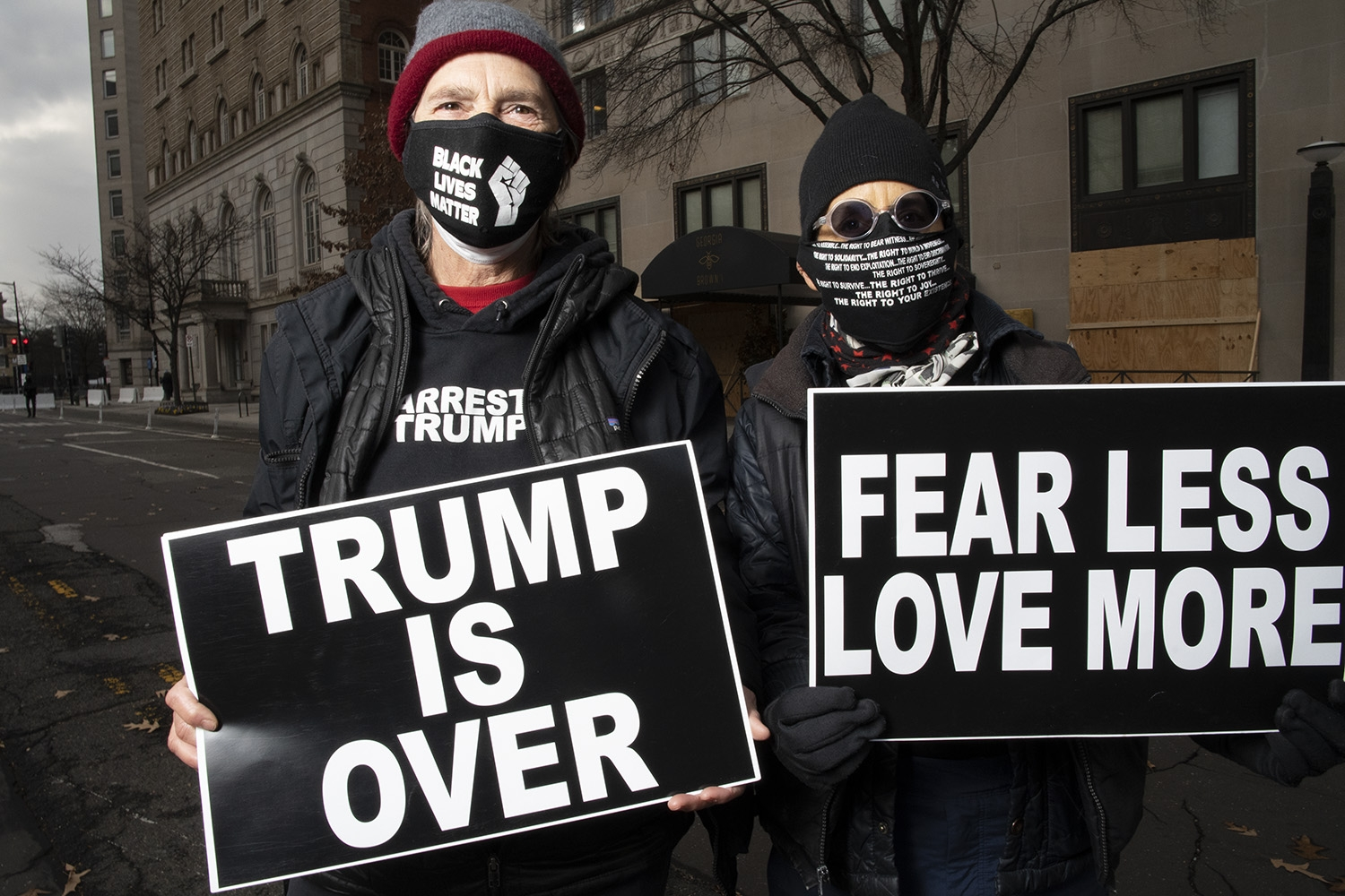 "Two protestors, dressed in black winter attire and wearing face masks stand on the streets of D.C. They are each holding a black sign with white lettering'; the sign on the left says ""Trump is Over"" and the sign on the right says ""Fear Less Love More""."