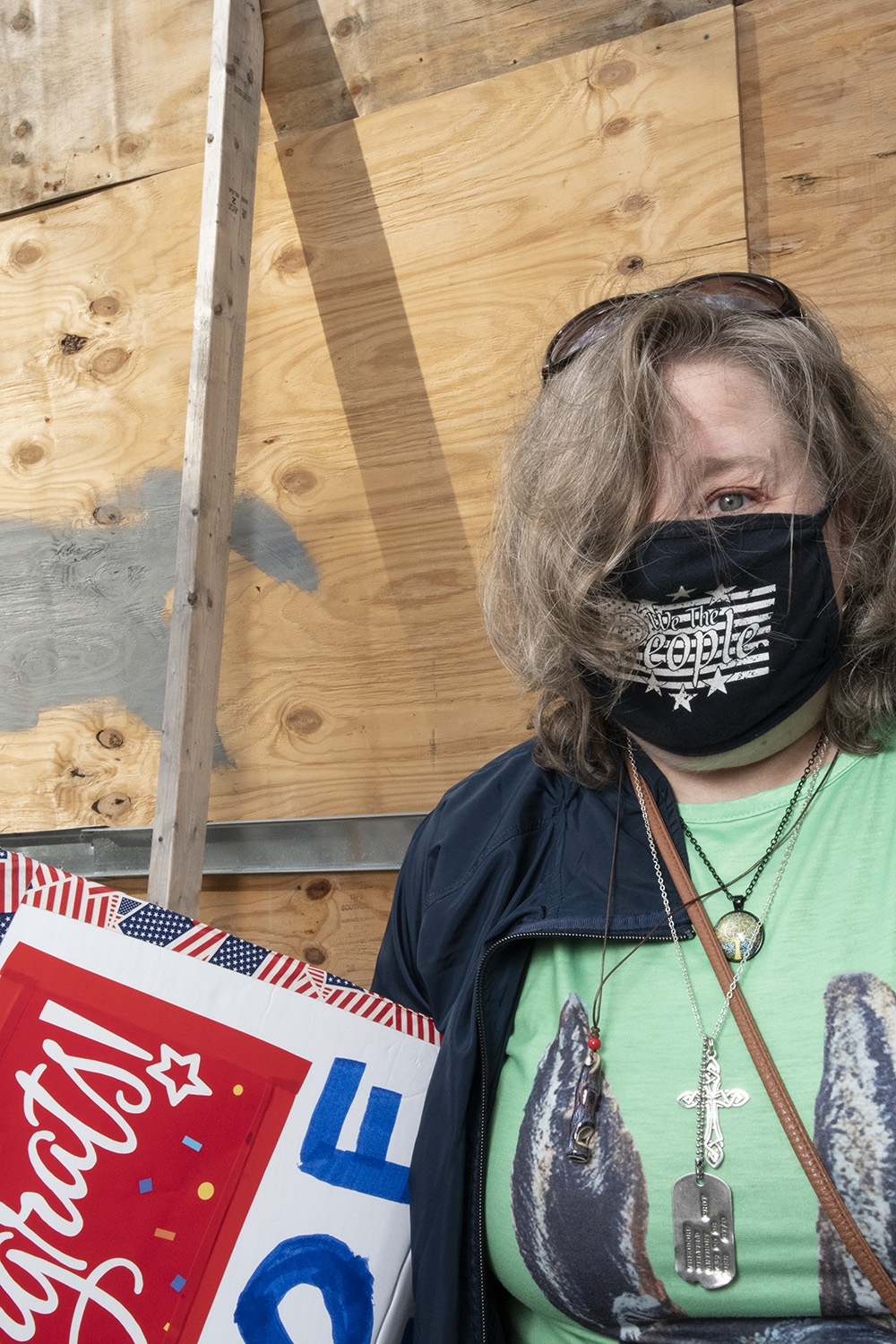 A white woman with blonde shoulder length hair, wearing a green shirt, blue jacket, a black mask, and a pair of dog tags stands in front of a chipboard barrier.