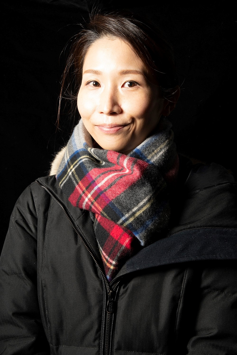An Asian woman with her dark hair pulled back from her face looks at the camera. She is smiling slightly and wears a red, grey, blue, and yellow plaid scarf tucked into a black winter jacker.