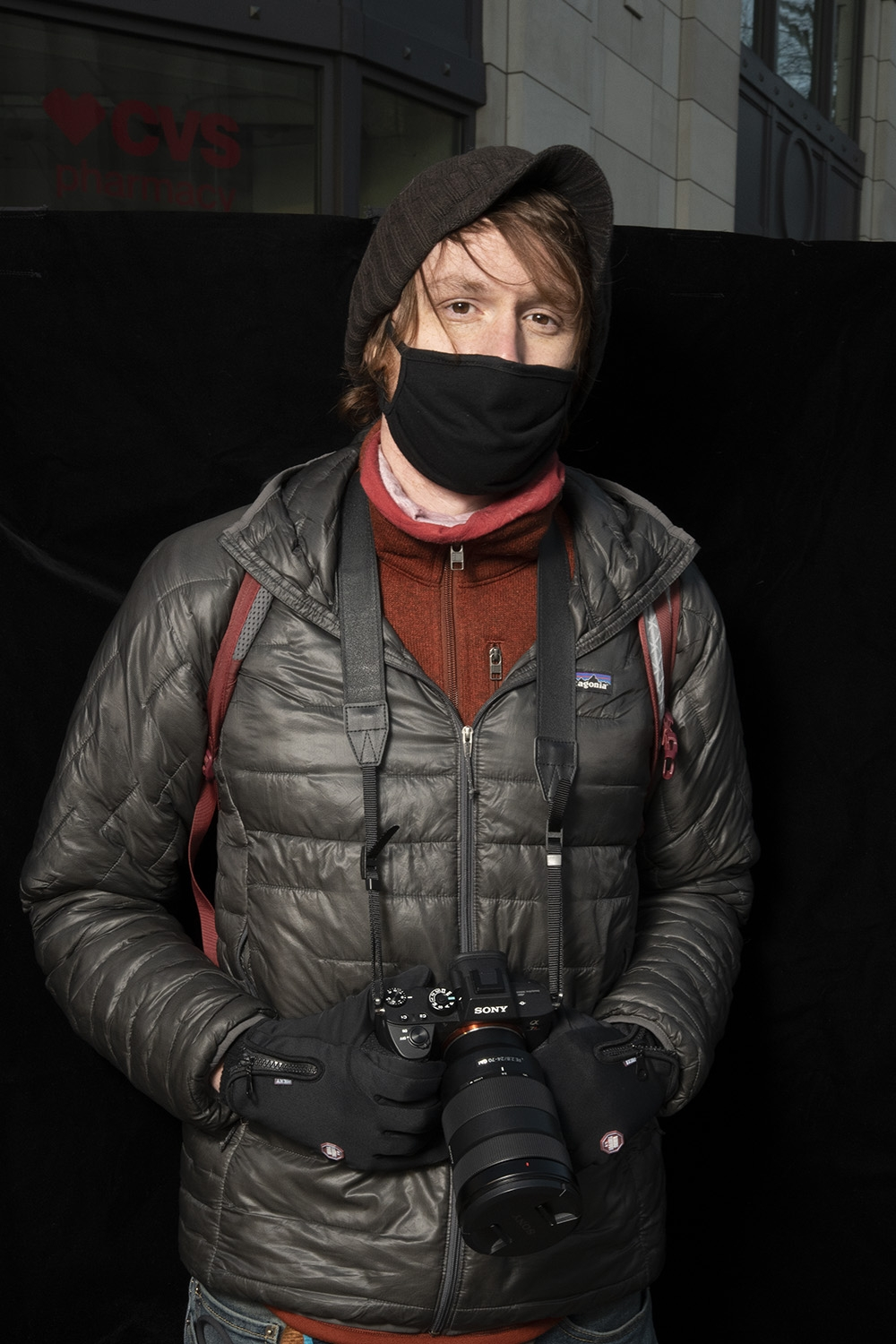 A white young man with red hair clutches a professional camera in his gloved hands. he is wearing a dark brown winter hat, a black face mask, black gloves, and a rust colored fleece jacket underneath a black puffer jacket.
