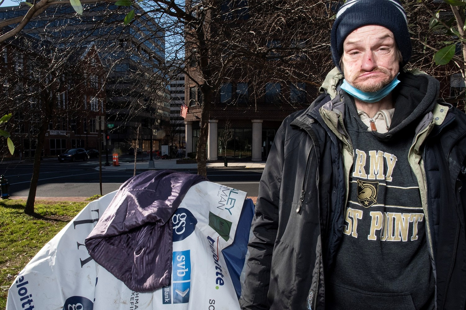 A homeless man stands in a park in downtown Washington D.C. The white middle-aged man has a blonde goatee and is wearing a navy winter hat, a blue surgical mask beneath his chin, an Army West Point gray sweartshirt and several layers of winter jackets.