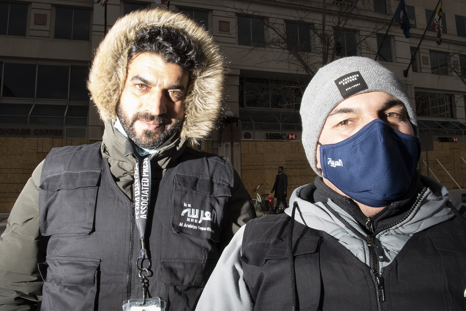 An image featuring two men. One the left, a man with dark hair and a dark goatee wears a black canvas vest over an army green winter coat with the fur lined hood pulled up over his head. The black vest features a patch with Arabic lettering. On the right, a shorter man wears a light grey winter hat, a blue facemask, a light grey winter jacket, and a black vest.