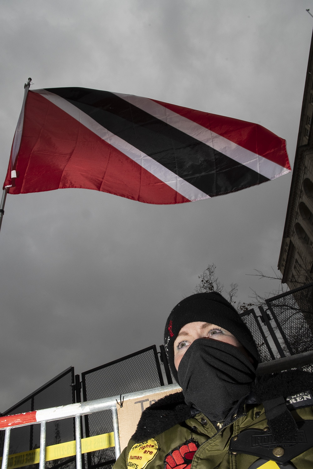 A red, white, and black flag flies against a grey skey. Below it, a white woman wearing a black knit hat, black face covering, and army green jacket looks off into the distance.