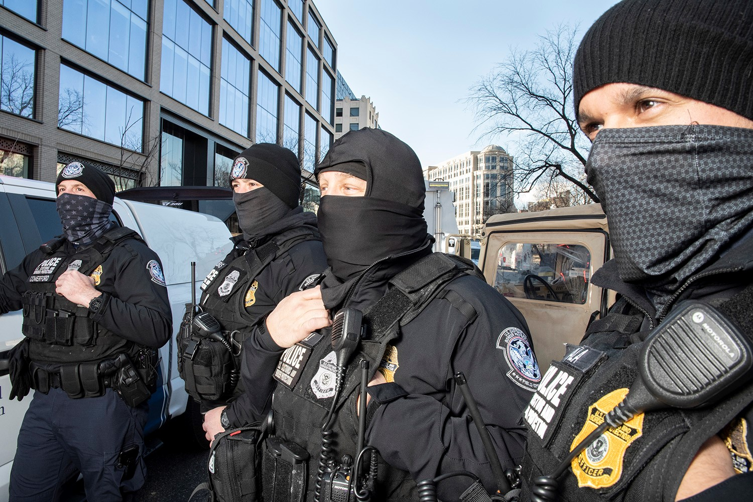 Four white men wearing black police uniforms and gear, black winter hats, and dark face masks, stand in front of law enforcement vehicles in the streets of downton D.C.