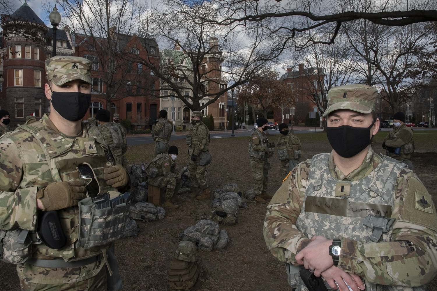Two white men wearing camoflage National Guard fatigues and black facemask look at the camera. Behind them, are other National Guardsmen standing a park in downtown D.C.