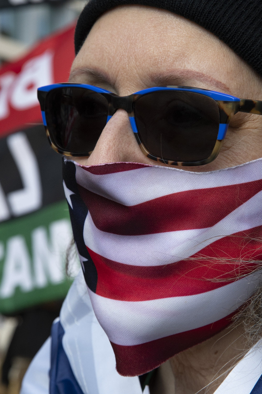 Image of a woman, wearing a black winter hat, tan and blue sunglasses, and an American flag bandana as a mask.