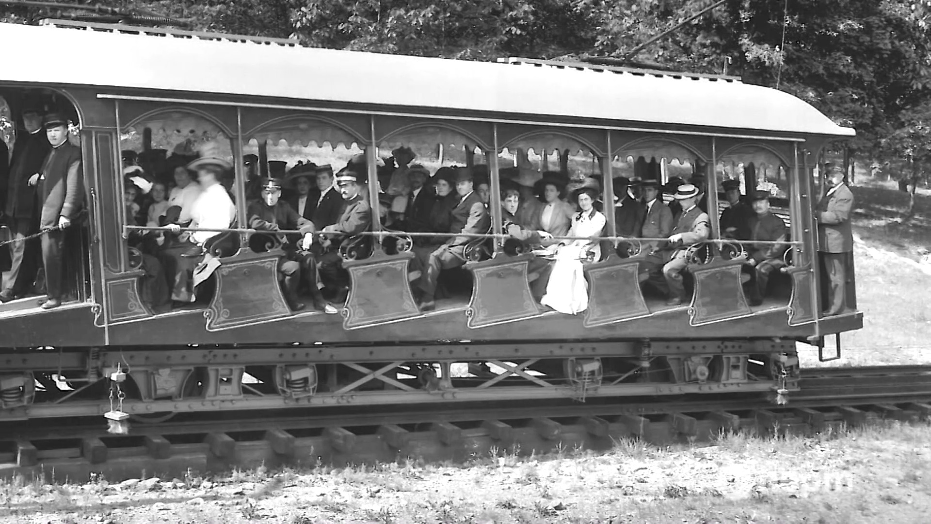 Vintage, black and white photo of men and women riding a train car on the Mt. Tom Inclined railroad.