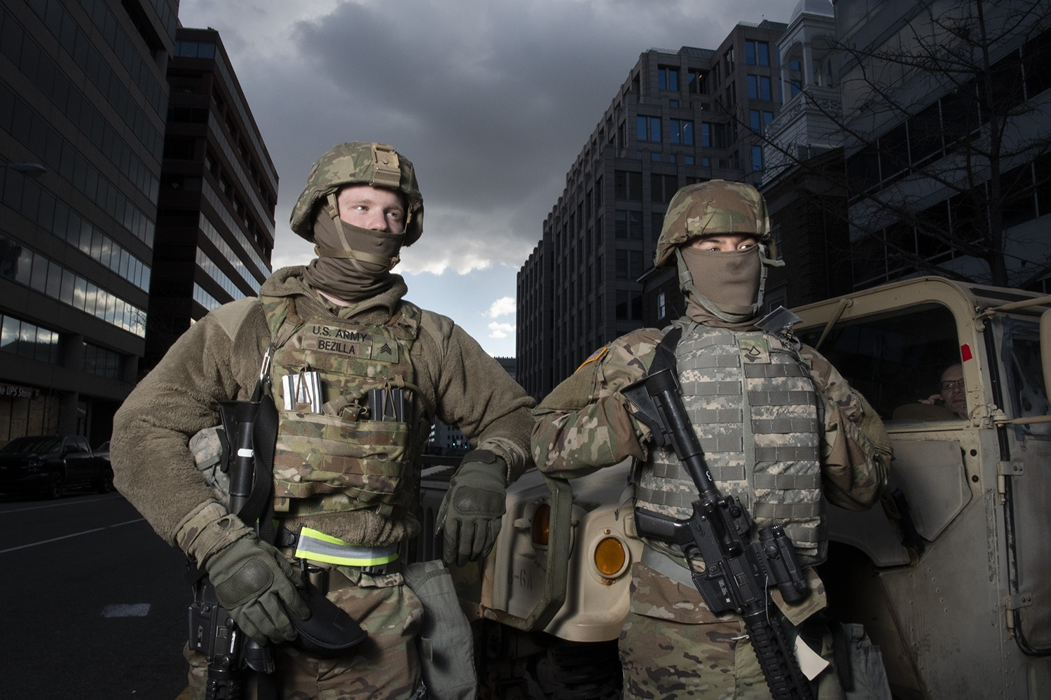 Two tropps wearing military fatigues and long, black guns stand in front of a tan military vehicle in downtown D.C.