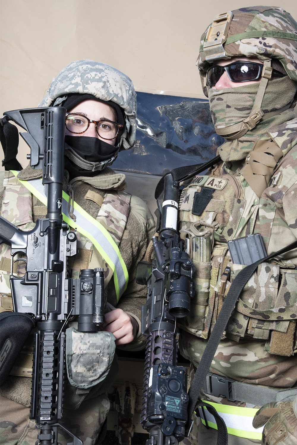 Two National Gaurdspeople, one a white female wearing glasses and one white male wearing sunglasses, wear military fatigues, helments, face coverings, and carry military rifles.