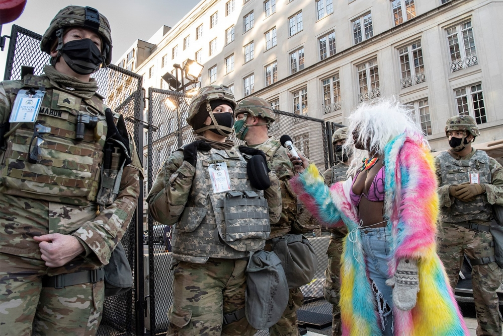 Several soldiers wearing military fatigues, helmets, and black masks stand in front of a mesh fence. In front of them, a black woman wearing a white wig, rainbow bow tie, magenta bikini top, faded blue jeans, and a pink, yellow, and blue tie-dyed furry coat holds a microphone.