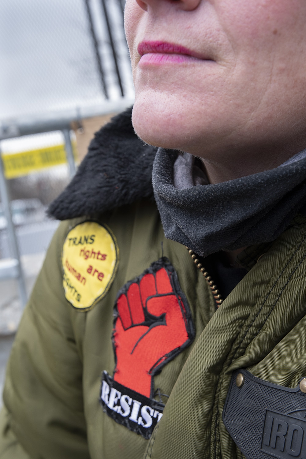 "Image of a white woman wearing pink lipstick from her nose to below her shoulders. She weats an army green jacket with a black fur collar, and a dark grey neck gaiter. On the jacket are a yellow patch that says ""Trans rights are human rights"" and a patch featuring a red fist that says ""Resist."""
