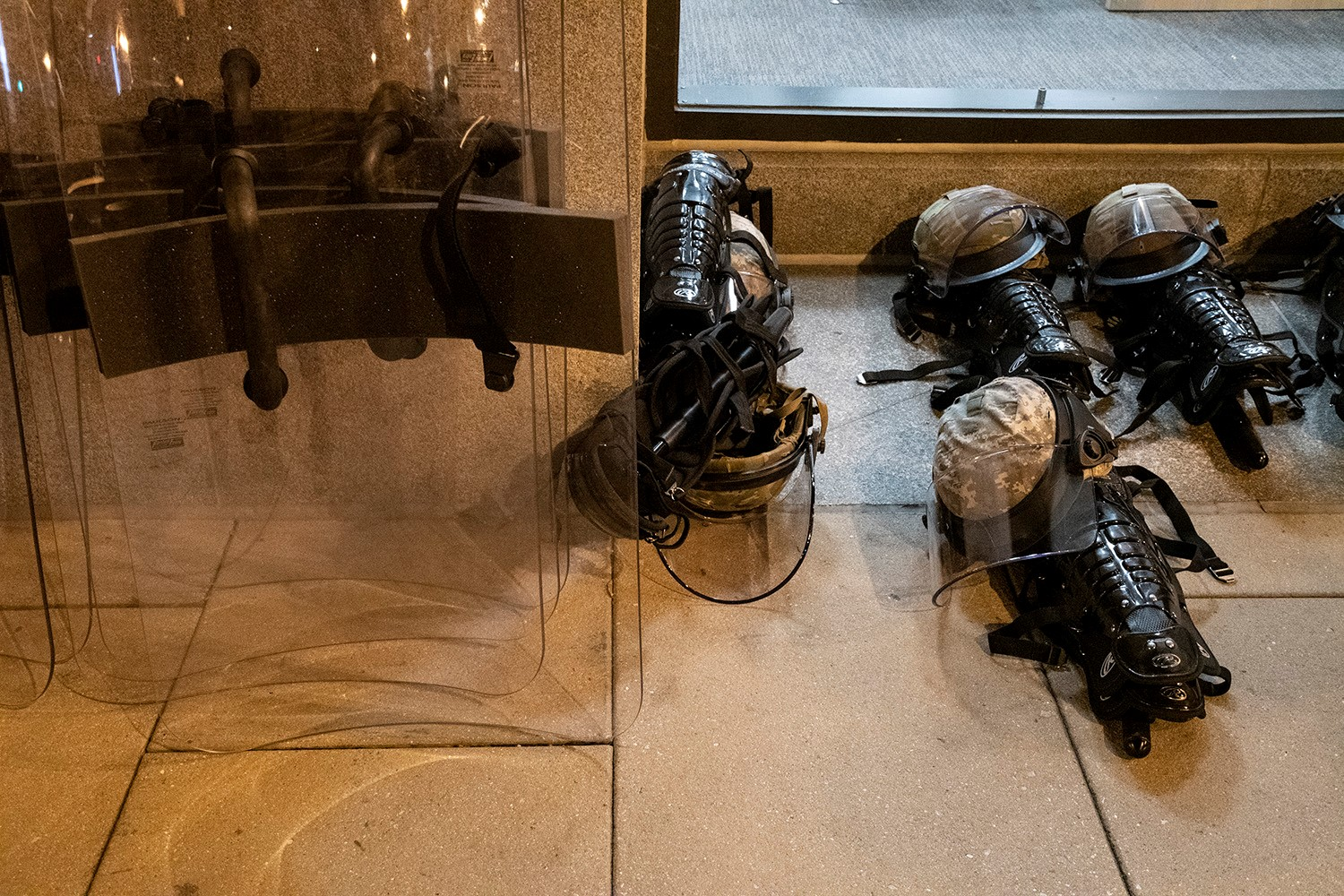 Riot gear, including clear plastic shield, helmets, and armor sit in neatly organized pills on a stone floor.