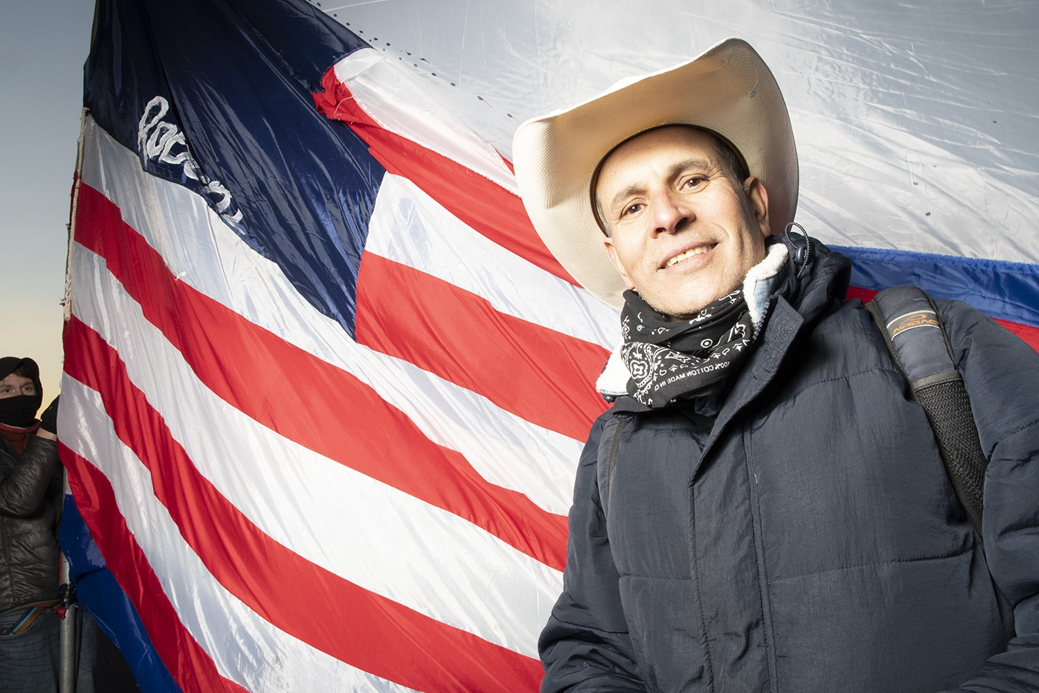 A slightly smiling Mexican man stands in front of a giant U.S. flag, which is missing its stars. The man wears a tan cowboy hat, a black bandana around his neck, and a navy winter jacket.