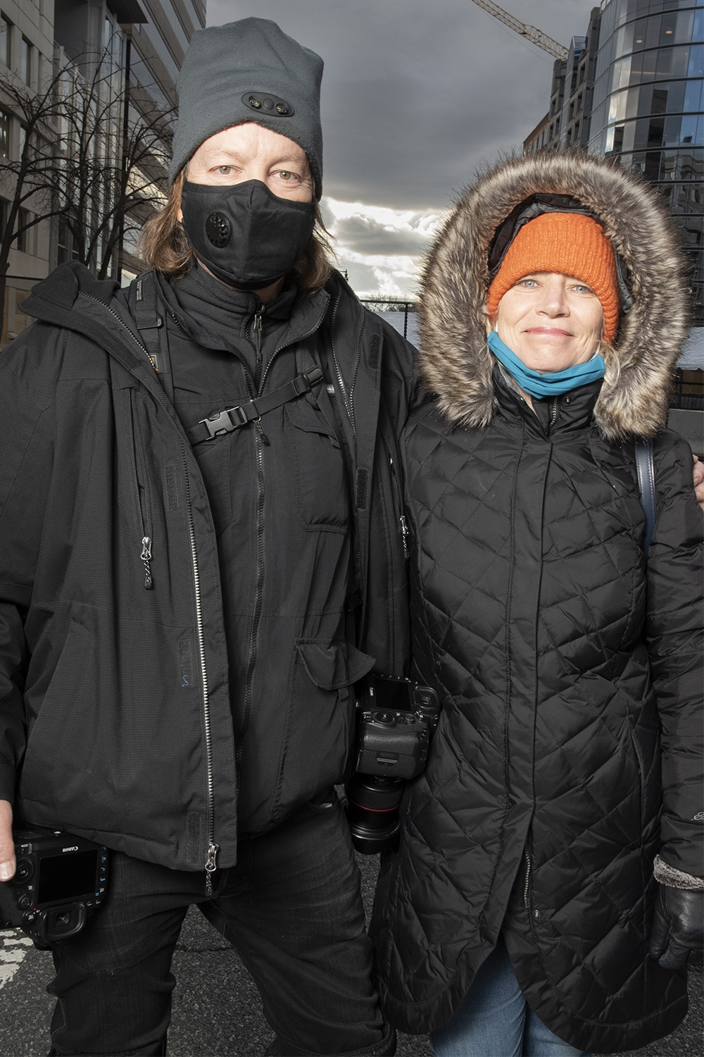 A man wearing a black jacket, black pants, a black face mask and a grey winter hat stands with his arm around a woman. Professional camera are slung over each of the man's shoulders. The woman, who is smiling, wears a black jacket with a fur-lined hood around her head, an orange winter hat, a black jacket, and black gloves, and she has a teal face mask tucked under her chin.