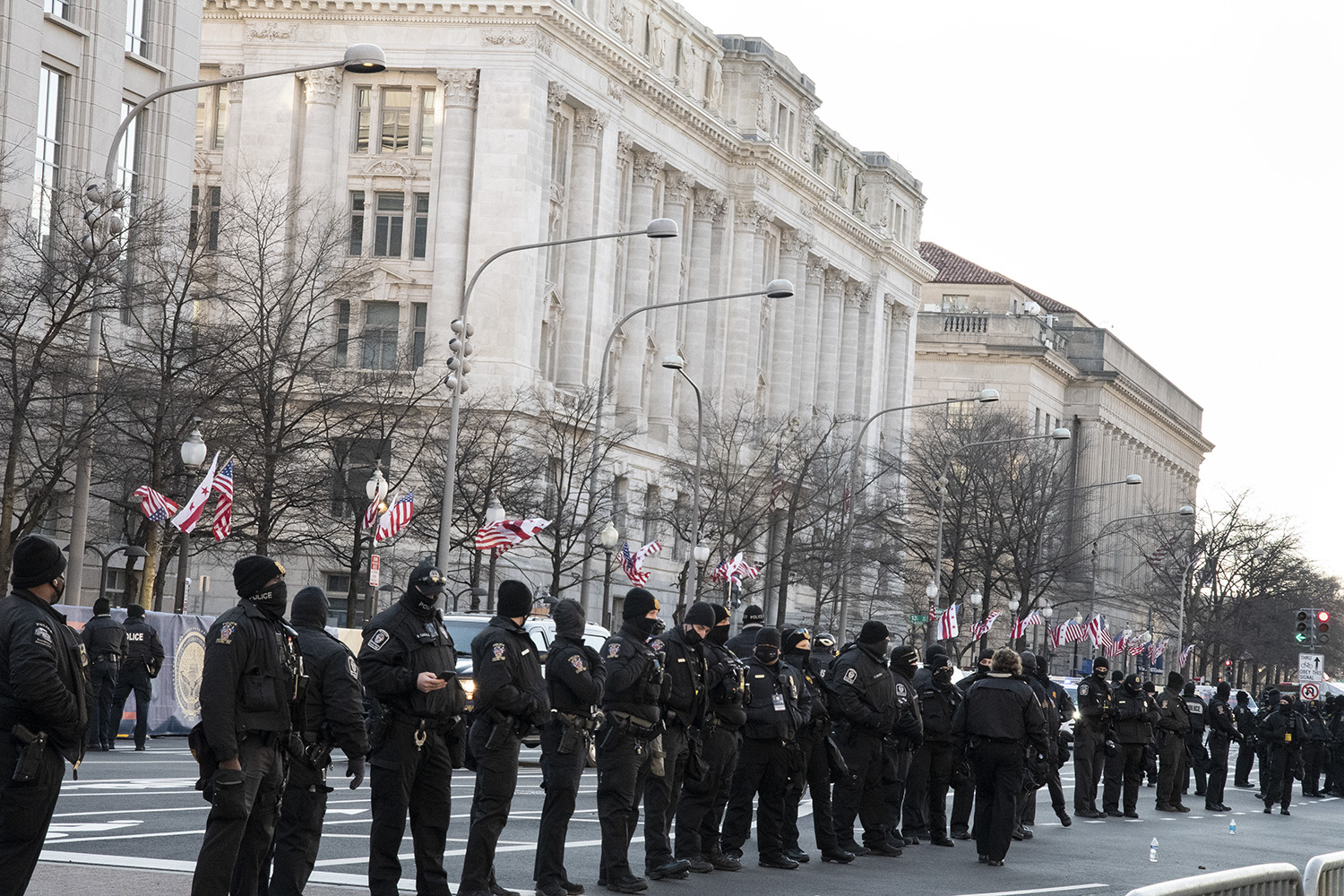 A line of police officers, most wearing black winter hates and black face coverings, line the street in front of the white stone buildings along Pennsylvania Avenue in Washington, D.C.