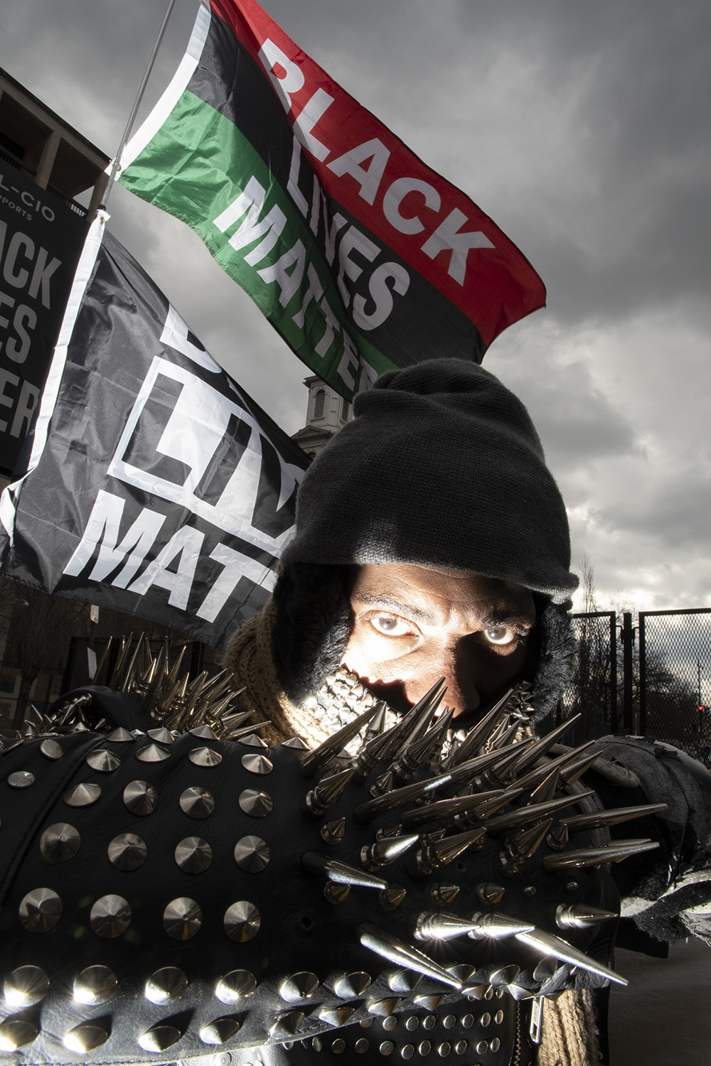 In a dramtic image, light hits the face of a man wearing a black winter hat and dark grey winter scarf. His arm, covered in silves spikes and studs, covers the lower half of his face. Behind him fly a red, black and green Black Lives Matter flag and a black and white Black Lives matter sign.