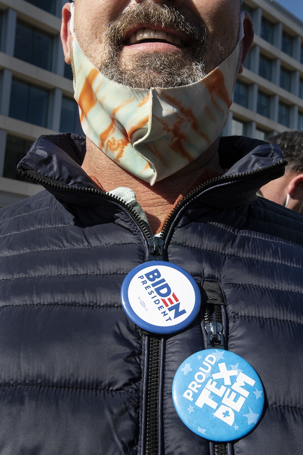 Image of a white man with a graying beard and mustache from the nose down. He is wearing a mint green and orange streaked facemask under his chin and a navy blue puffer winter jacket. On his jacket are two buttons: a red, white, and blue button that says BIDEN PRESIDENT and a light blue button that says PROUD TEX DEM.