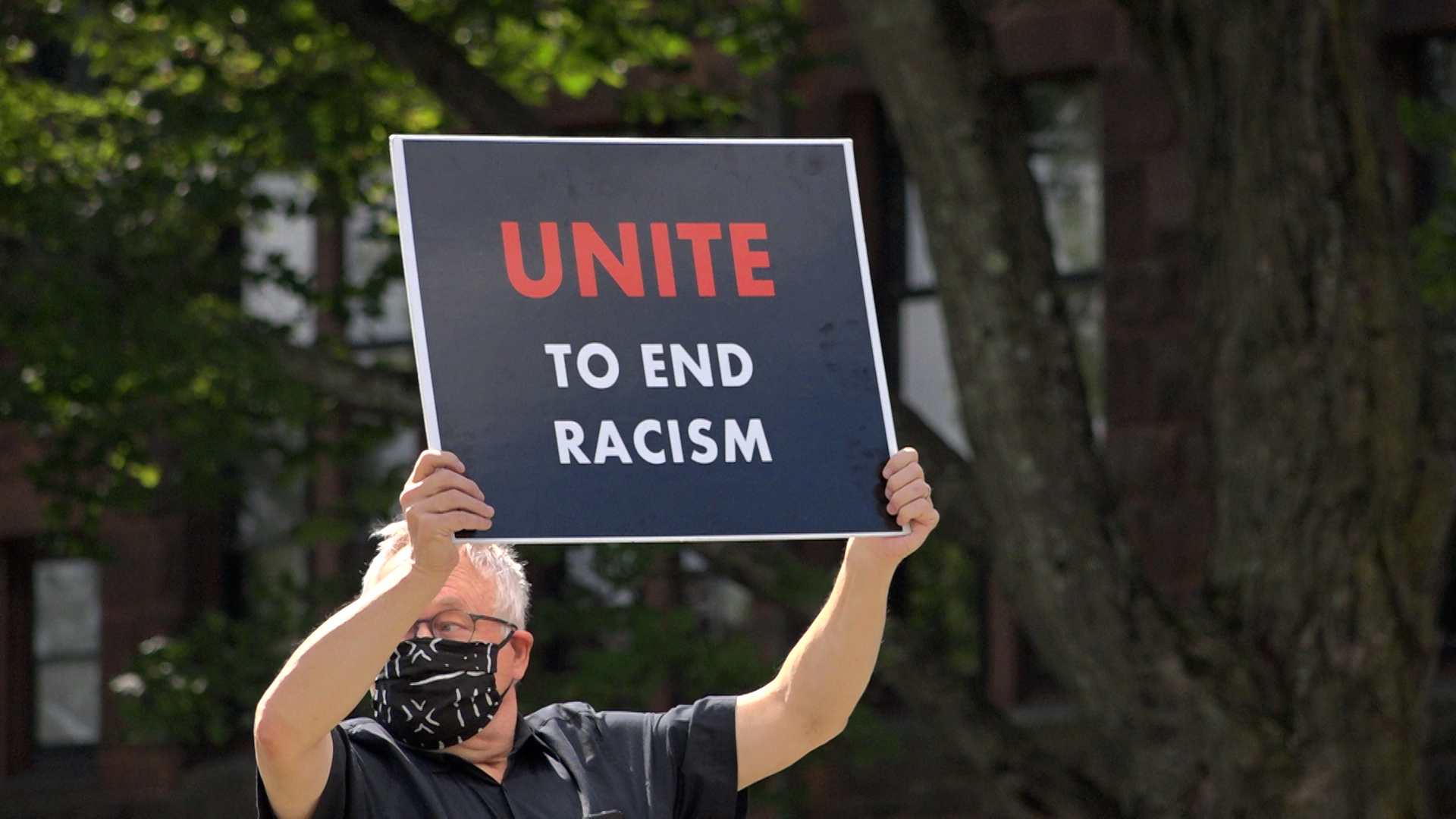 "An older white man holds a sign that says ""Unite to End Racism"" at a Racial Justice vigil in South Hadley, MA."